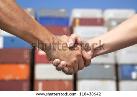 two business man handshaking before stack of containers - stock photo