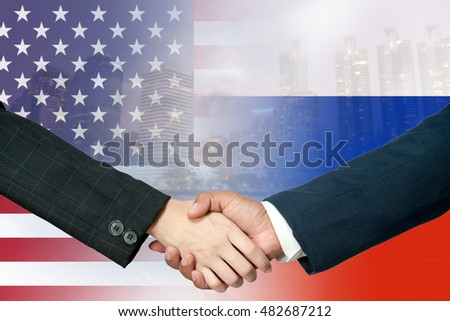two business man shakehand with usa and rusia flag as a background