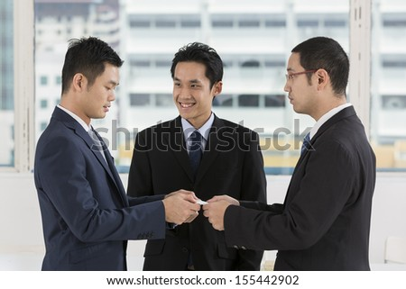 Two business men exchanging business cards. Caucasian and asian business men swapping business cards