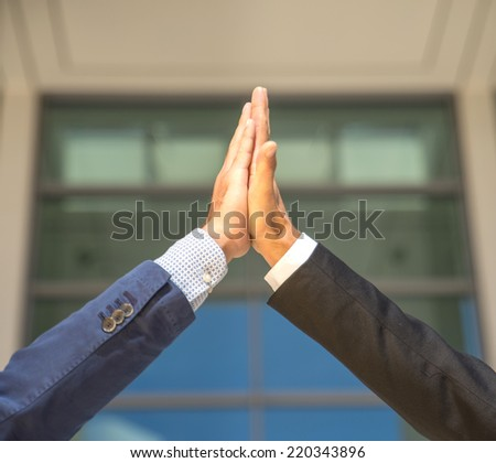 Two business men giving a high five to each other.High five concept for success, teamwork, congratulating and celebration  - stock photo