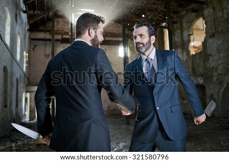 two business men making a deal but hiding knives - stock photo