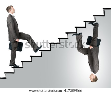 Two business men walking up stairs in different sides