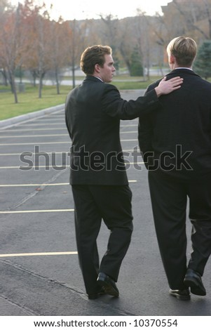 two business men walking with one man placing hand on back. - stock photo
