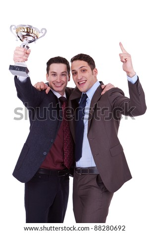 Two business men winning a trophy on white background - stock photo