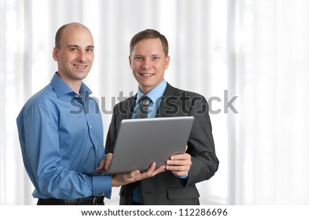 Two business men with laptop in office