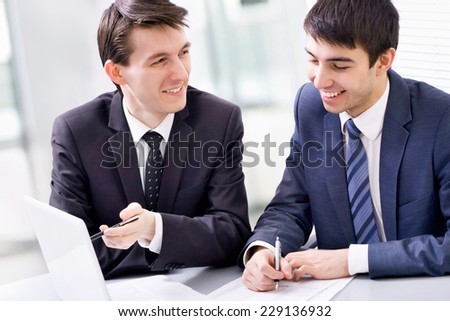 Two business men working together on laptop in the office - stock photo