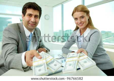 Two business partners at workplace giving money and looking at you - stock photo