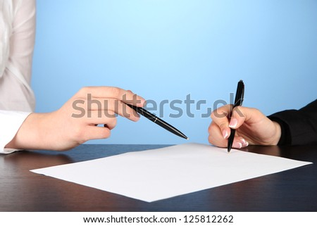 Two business partners signing document, on blue background