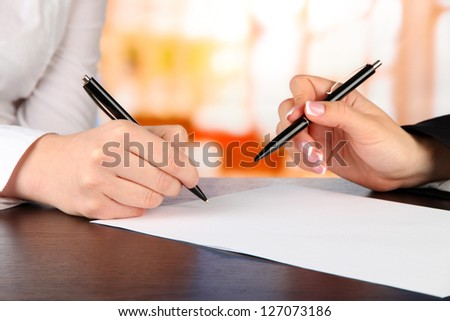 Two business partners signing document, on bright background - stock photo