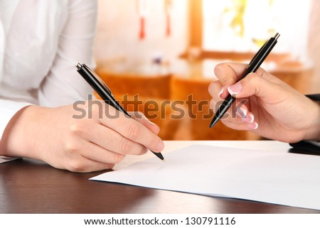 Two business partners signing document, on bright background