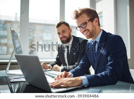 Two business partners working with laptop together - stock photo