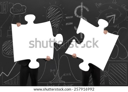 Two business people assembling blank white jigsaw puzzles on business concept doodles background - stock photo
