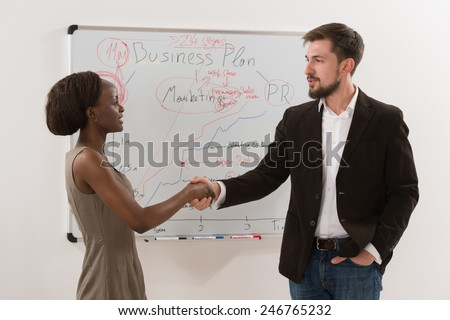 Two business people businessman and businesswoman making agreement in front of white board - stock photo