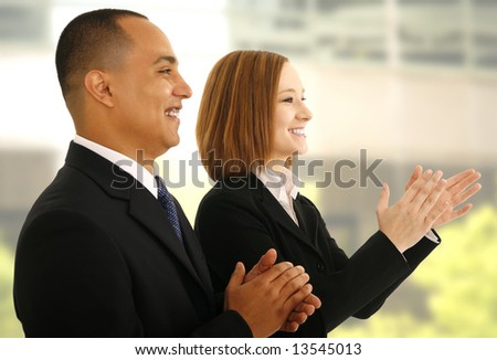 two business people clapping hand in office environment as if they are responding to presentation