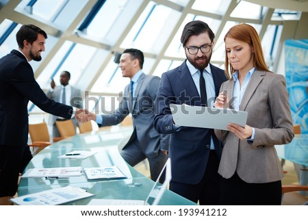 Two business people discussing data or planning work on background of their colleagues handshaking - stock photo