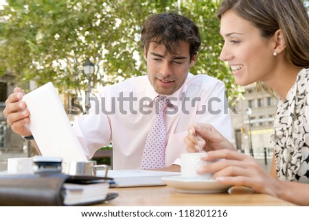 Two business people having a meeting and using technology outdoors, while having a coffee in a coffee shop terrace.