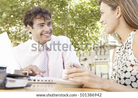 Two business people having a meeting in an outdoors cafeteria in the city, smiling. - stock photo