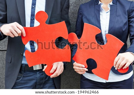 Two business people holding two big red jigsaw puzzle pieces