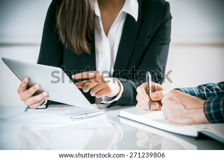 Two business people in a meeting discussing information on a tablet-pc and taking notes as they work together as a team, close up view of their hands seated at a desk - stock photo