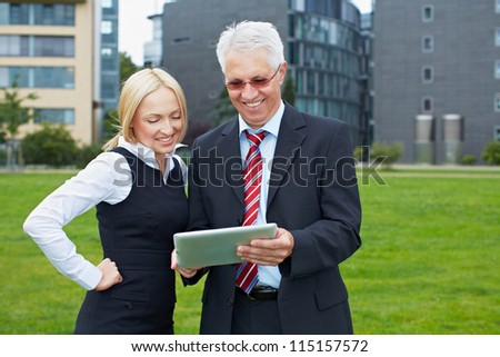 Two business people in a park looking at a tablet computer