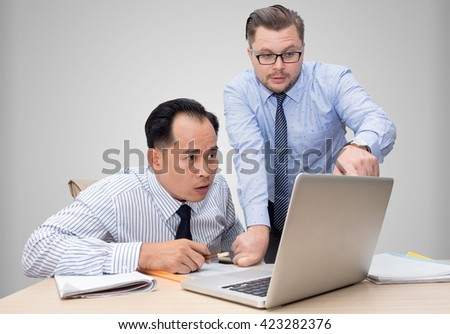 Two business people in bright shirts sitting at desk working in team together, discussing the problem, point finger on laptop