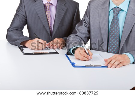 Two business people in elegant suits sitting at desk working in team together, working with documents sign up contract, on clipboard, folder with papers, business plan. Isolated over white background. - stock photo