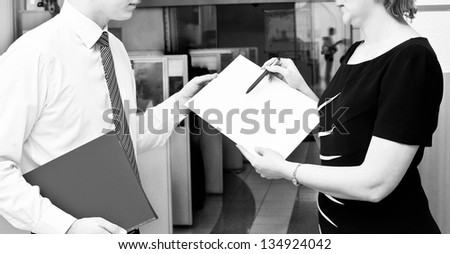 Two business people in elegant suits standing working in team together and discussing the problem looking into clipboard, folder with papers, document, business plan.  over interior background. - stock photo