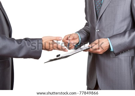 Two business people in elegant suits standing working in team together and discussing the problem looking into clipboard, folder with papers, document, business plan. Isolated over white background. - stock photo