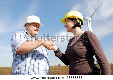 two business people in front of a wind park