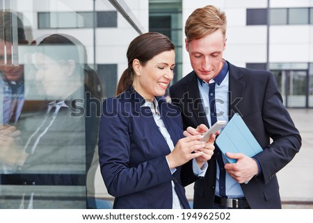 Two business people looking together at smartphone in the city - stock photo