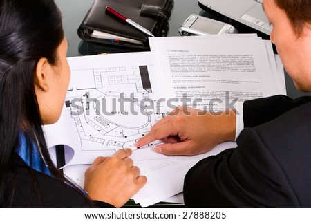 Two business people, man and woman discuss about their property planning. - stock photo