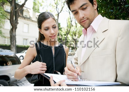 Two business people meeting outdoors in a tree aligned street. - stock photo