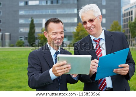 Two business people outside looking at a tablet computer - stock photo