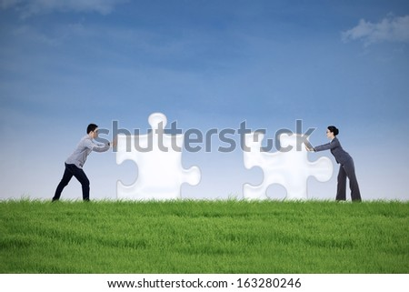 Two business people putting together two puzzle pieces on the meadow - stock photo