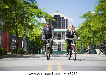 Two business people riding bicycle to work, can be used for gas savings concept - stock photo