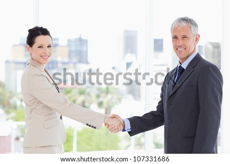 Two business people shaking hands while smiling and looking at the camera - stock photo