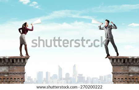 Two business people shouting in megaphones at each other - stock photo