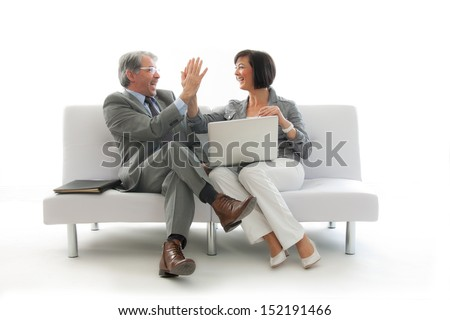 Two business people sitting and working together on a white sofa  - stock photo