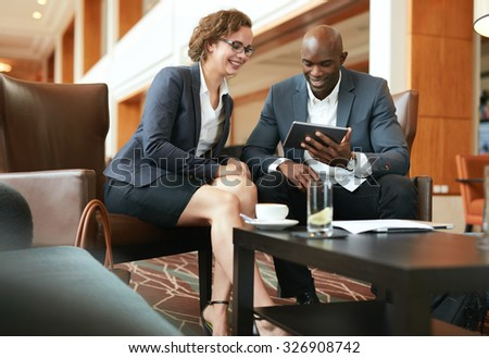 Two business people sitting at coffee shop discussing project on digital tablet. Young businesswoman and businessman looking at tablet computer smiling. - stock photo