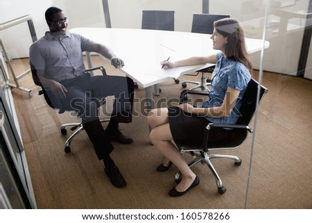 Two business people sitting at conference table and discussing during business meeting - stock photo