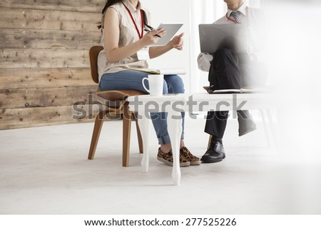 Two business people sitting in the chair discussing - stock photo