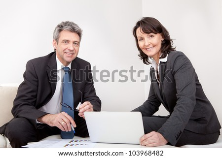 Two business people sitting in the couch discussing