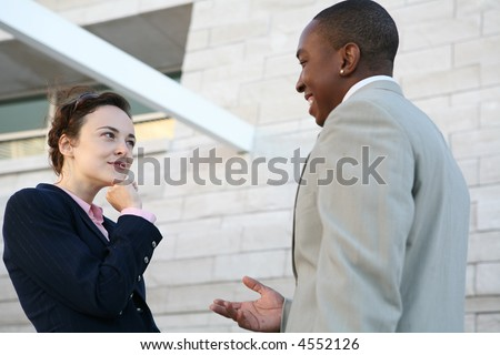 Two business people talking outside the company - stock photo