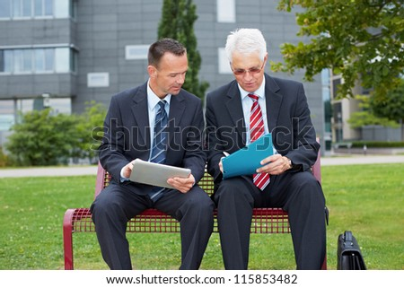 Two business people with tablet computer signing contract on a park bench - stock photo