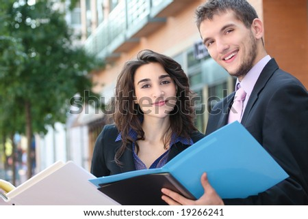 Two business people, young professionals, outdoors, at work - looking at folders. Suitable for a variety of political, economic themes - stock photo
