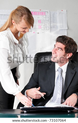 two business persons are discussing plans at office
