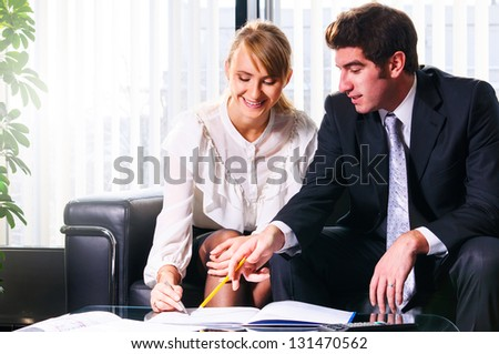 two business persons are sitting and discussing on leather sofa at office - stock photo