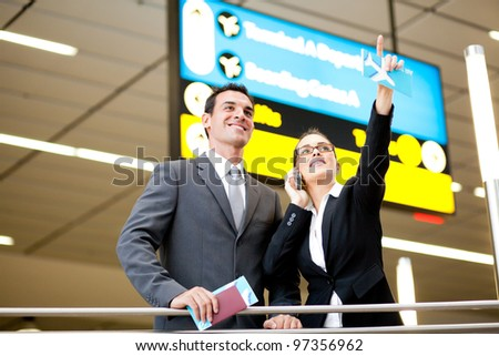 two business travellers checking boarding information at airport - stock photo
