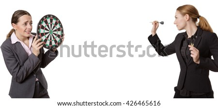 two business woman one holding a dartboard and one throwing darts