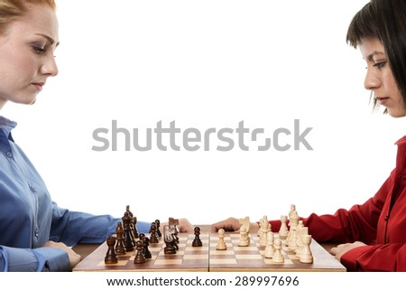 two business woman playing chess together trying to out think each other - stock photo